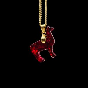Alpakaförmiges rotes Rubin-Schmuckstück mit goldenem Anhänger und Kette auf schwarzem Hintergrund. Symbolisiert das Krafttier Alpaka