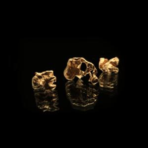24K Vergoldete Kupfer Nuggets auf schwarzem Hintergrund.