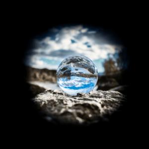 Kristallkugel aus Glas welche die im Hintergrund liegende Landschaft reflektiert. Der Rand des Bildes ist schwarz.