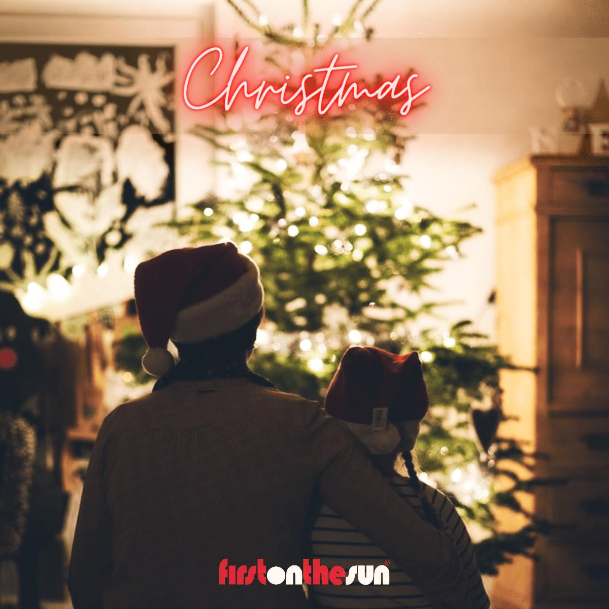 Mann mit Kind im Arm vor einem Weihnachtsbaum mit Christmas Beschriftung. Symbolbild für spirituelle Adventskalender mit Edelsteinen und Kristallen
